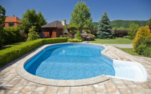 In-ground pool with steps and stone patio area with houses and trees in the background