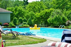 Yellow inflatable duck floating in a backyard swimming pool